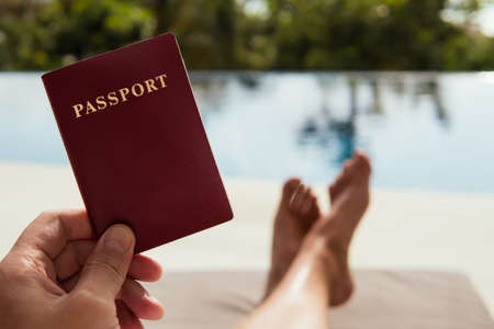 Man holds a passport in his hand on the tropical background Stock Photo