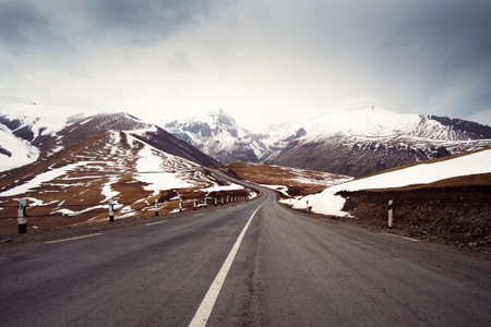 Winter road stretching into the distance among the mountains and cloudy sky Stock Photo