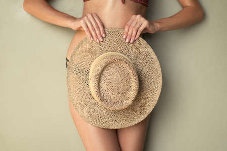 Slim female body in a swimsuit and a beach hat on an olive background