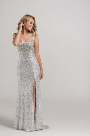 Attractive girl in a shiny evening dress made of diamonds.