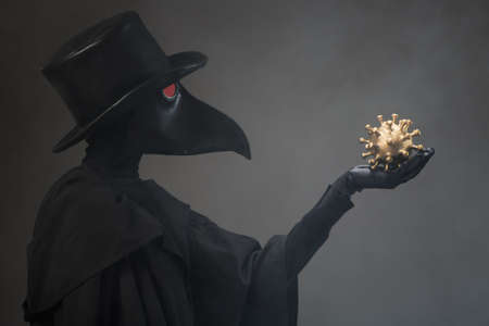 The plague doctor holds a golden model of the virus in his hand.
