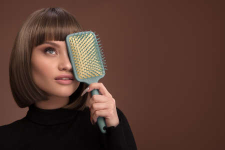 Portrait of a beautiful brown-haired woman holding comb in her hand. Brown background. Standard-Bild