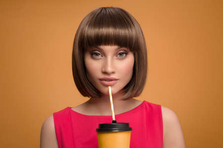 Portrait of a beautiful woman holding cup of coffee takeaway in her hand. Yellow background.