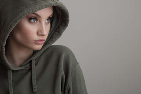 Beautiful young girl dressed in a hoodie on a gray background Standard-Bild