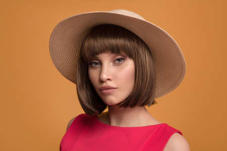 Portrait of a beautiful brown-haired woman in a hat on a yellow background.