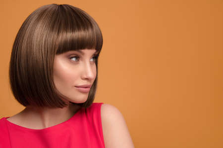 Portrait of a beautiful brown-haired woman with a short haircut on a yellow background.