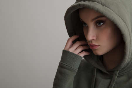 Beautiful young girl dressed in a hoodie on a gray background