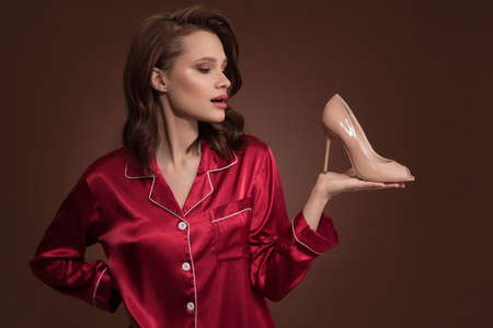 Lovely girl in red silk pajamas holding one shoe in her hand on brown background.
