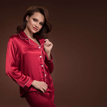 Pin-up girl in red silk pajamas on brown background Standard-Bild
