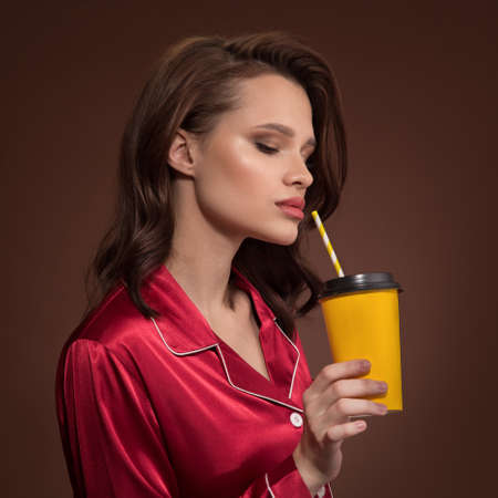 Portrait of a beautiful woman holding cup of coffee takeaway in her hand. Brown background.