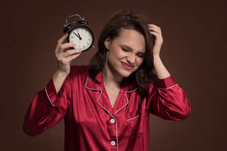 An angry girl in pajamas holds an alarm clock in her hand. Brown background. Standard-Bild