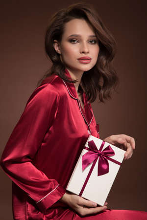Portrait of a beautiful woman holding gift box in her hand. Brown background. Standard-Bild