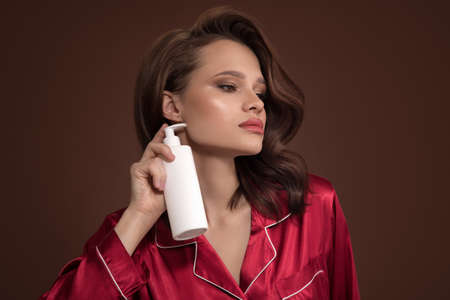 Portrait of a beautiful woman holding shampoo in her hand. Brown background.