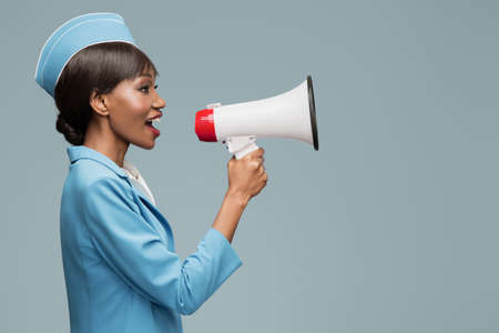 Cheerful young african stewardess shouts into the loudspeaker. Blue background. Standard-Bild