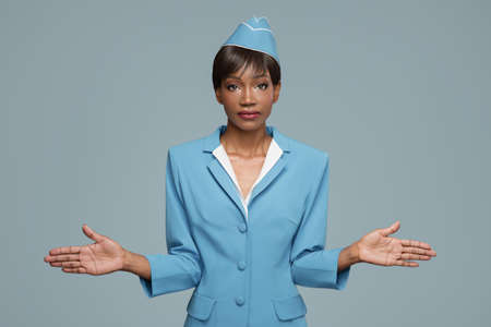 Young african stewardess giving safety briefing. Blue background. Standard-Bild