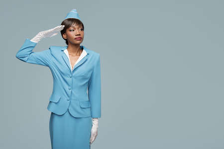 Confident young african stewardess. Blue background.