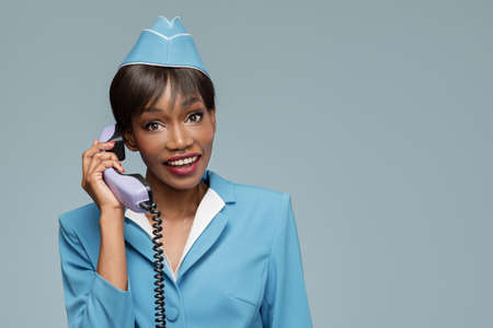 Cheerful young african stewardess talking on retro phone. Blue background.