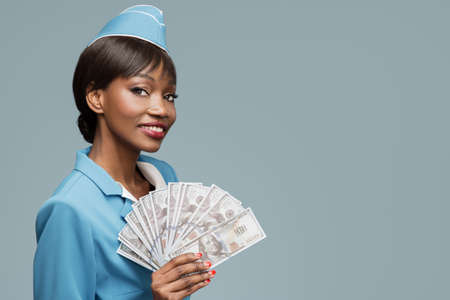 Cheerful young african stewardess holding money in hand. Blue background.