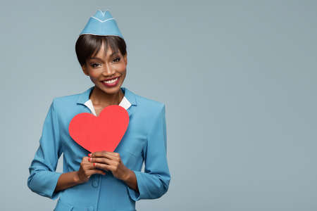 Lovely young african stewardess holding red paper heart in her hand. Blue background.