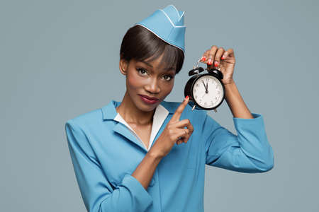 Cheerful young african stewardess holding an alarm clock in her hand. Blue background.