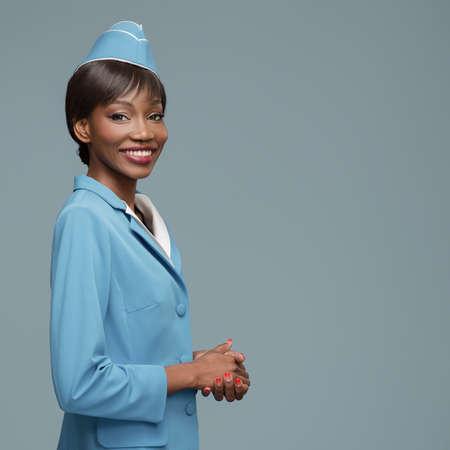 Cheerful young african stewardess. Blue background. Standard-Bild
