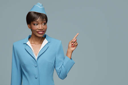 Cheerful young african stewardess points a finger at copyspace. Blue background. Standard-Bild