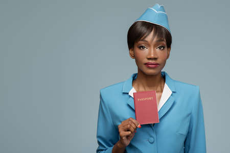 Confident young african stewardess holding passport in her hand. Blue background.
