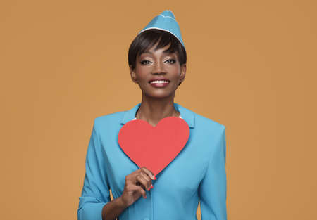 Lovely young african stewardess holding red paper heart in her hand. Orange background.