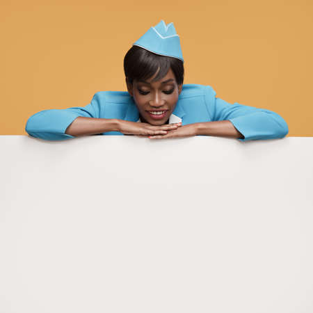 Smiling young african stewardess looking on white empty billboard. Orange background.