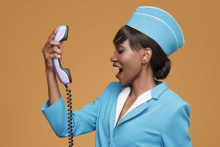 Cheerful young african stewardess talking on retro phone. Orange background.