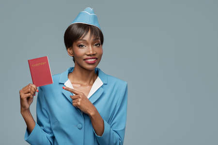 Smiling young african stewardess holding passport in her hand. Blue background. Standard-Bild