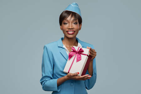 Smiling young african stewardess holding gift box in her hand. Blue background.
