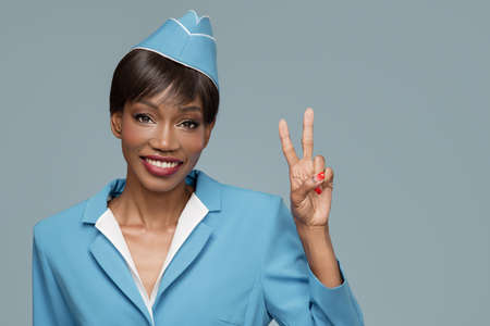 Smiling young african stewardess shows a positive gesture. Blue background.