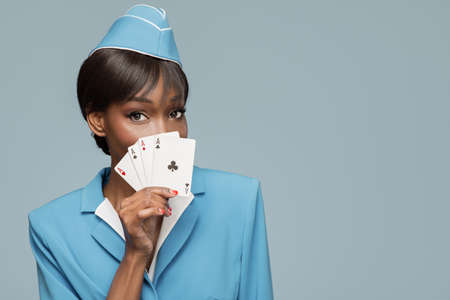 Lucky cheerful african stewardess holding four aces in her hand. Blue background. Standard-Bild
