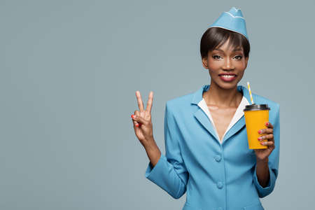 Cheerful young african stewardess holding a cup of takeaway coffee. Blue background.