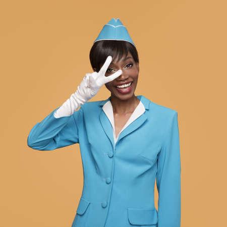 Smiling young african stewardess shows a positive gesture. Orange background. Standard-Bild