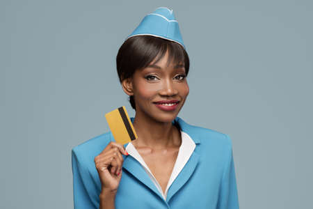 Smiling young african stewardess holding credit card in her hand. Blue background. Standard-Bild