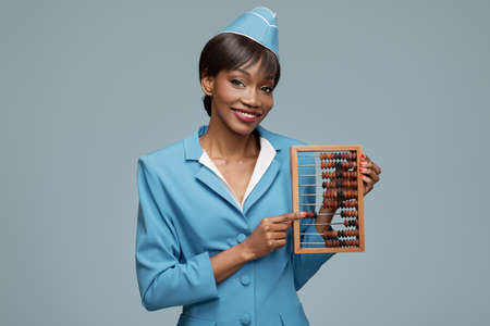 Smiling young african stewardess holding wooden abacus. Blue background.