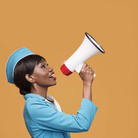 Cheerful young african stewardess shouts into the loudspeaker. Orange background.