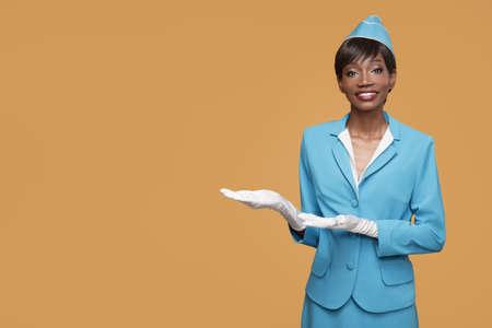 Smiling young african stewardess shows a welcome gesture. Orange background. Standard-Bild