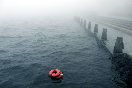 bad weather with mist on the embankment with redlife-buoy on the water photo