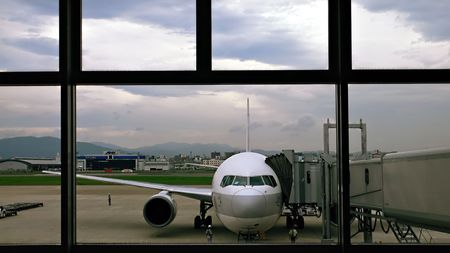 airplane close to the boarding gate, view from wide airport window