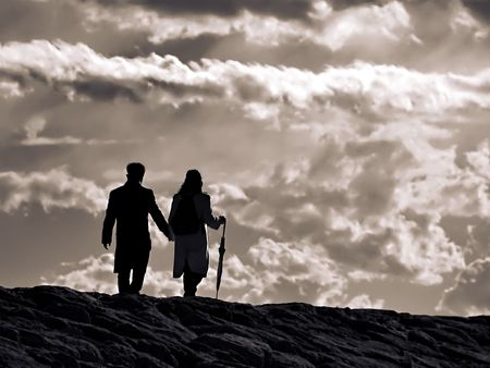 young couple walking  on the stormy sky background along seacoast