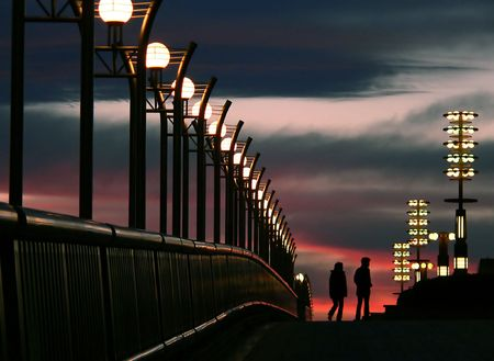 young couple walking between city lights and stormy evening sky in Tokyo Japan photo