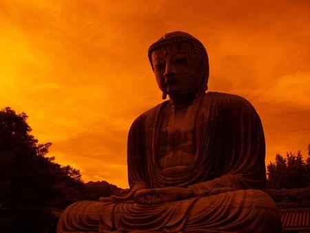 giant bronze Buddha statue in Kamakura Japan with dramatic sky background - taken with orange filter