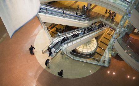interior of modern futuristic building - public hall of Japanese airport with moving escalators and people crowd photo