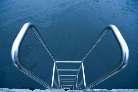metallic stairs: metallic stairs with hand-rails on the swimming pool water background Stock Photo