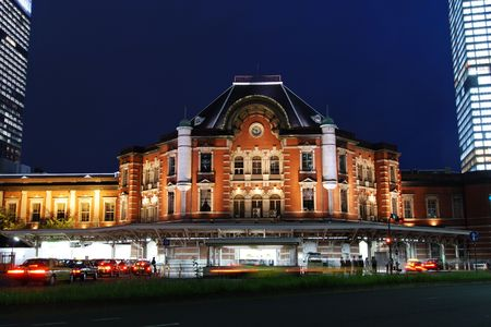 old building of Tokyo railway station build in 1914 at twilight time with many taxi-cars among huge modern buildings, Japan