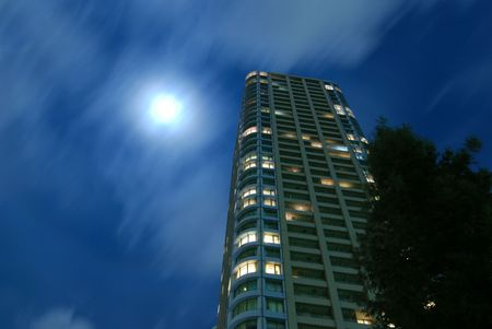 fool moon: high-rise residential building with fool moon scattering in moving clouds at windy night in Tokyo city, Japan