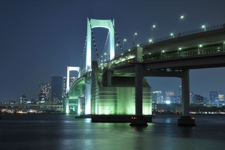 one of famous Tokyo landmarks, Tokyo Rainbow bridge over bay waters with scenic night illumination